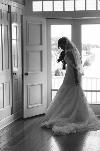 Bride standing against wooden door