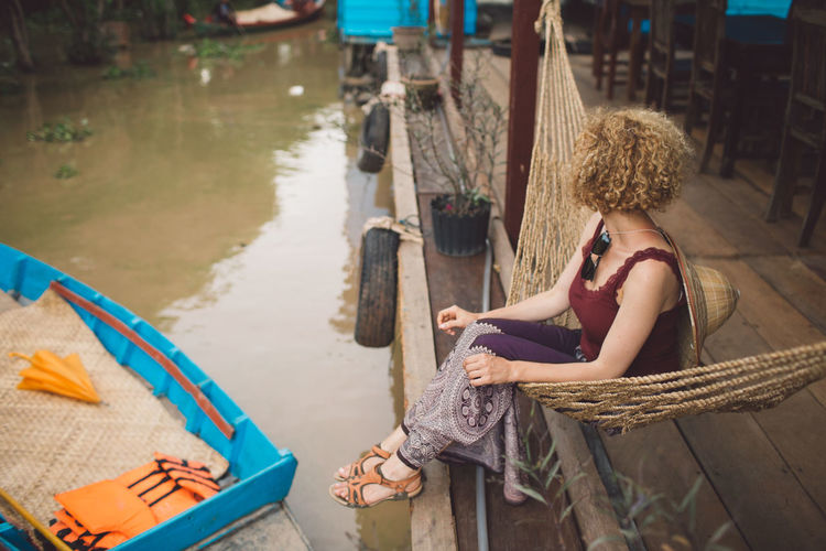 Woman Sitting In Hammock By Canal