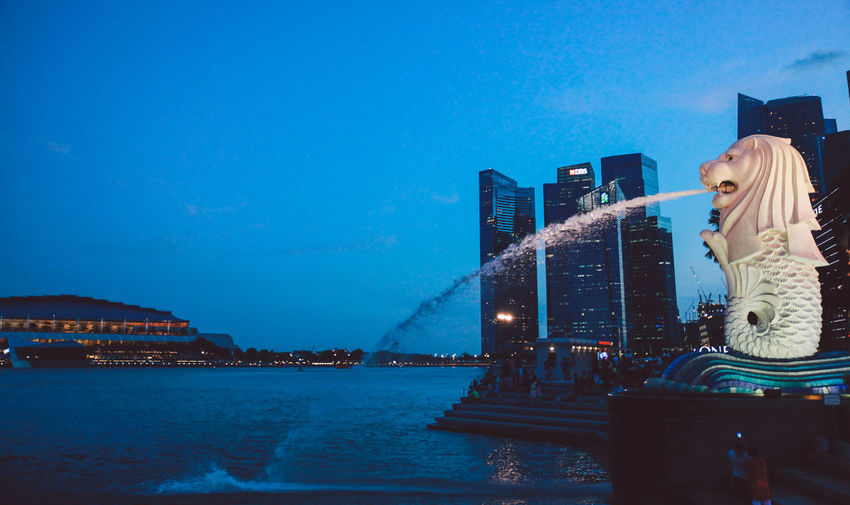Architecture Bay Building Exterior Built Structure City Cityscape Clear Sky Copy Space Dusk Dusk In The City Illuminated Marina Bay Merlion Modern Night Reflection Sea Sky Skyscraper Tall - High Tower Water Waterfront Blue Wave Cities At Night Connected By Travel