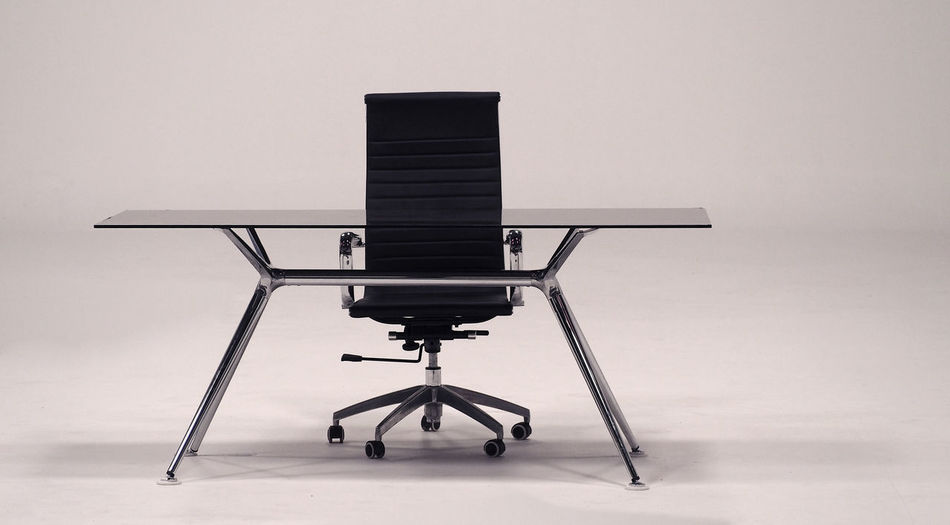 Office chair by table against gray background