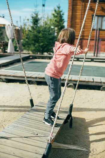 Full length of boy on swing in playground