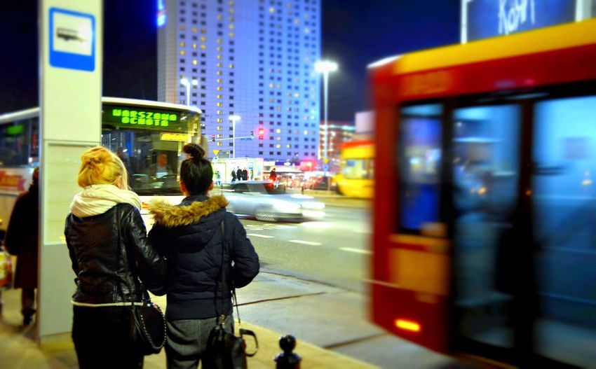Rear view of women standing on sidewalk by blur bus on street at night