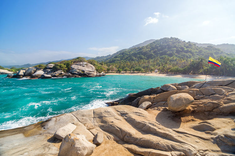 Colombian Flag On Rock In Sea At Tayrona National Park
