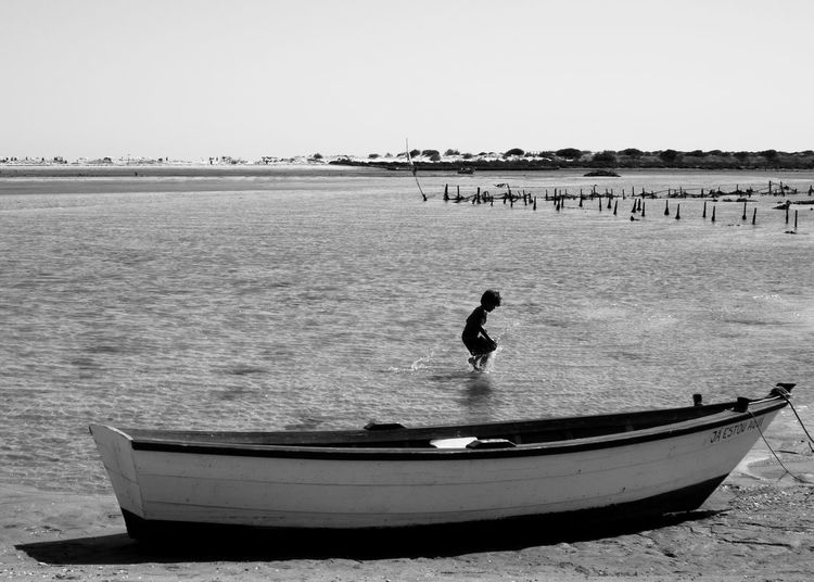 Summer Boat Boats Fish Boat Kid Kids Kidsphotography Kid In Beach Kid Playing Water Kid Playing Algarve Algarve, Portugal Portugal Portugese Beach Portugese Outdoors Water Full Length Sea One Man Only One Person Day Tranquility Nature Beach People Clear Sky Beauty In Nature An Eye For Travel