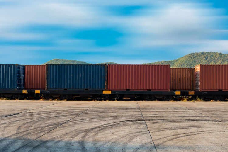 Containers shipping Box Container Ship Distribution Goods Industrial Industry Logistics Shipping Containers Sky And Clouds Transport Transportation Backgrounds Export Heavy Industry Import Mountain Shipping Terminal Shipping Yard Supply Train