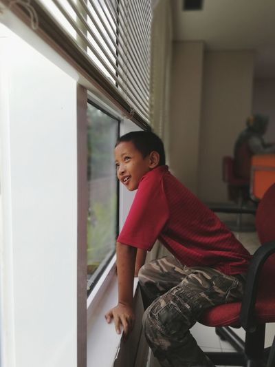 Portrait of boy sitting by window at home