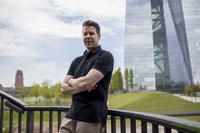 Man standing outside wearing casual clothing in front of a skyscraper in Germany. Looking at the camera. Adult Cloudy Day In Shape Khaki Pants Low Angle View Man Standing Arms Crossed Casual Clothing Caucasian Ethnicity Clouds Facing Camera Fit Glass Golf Shirt Handsome Male Medium Shot Model Office Building Posing Rail Sky Skyscraper Smile