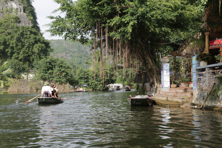 People on river against trees