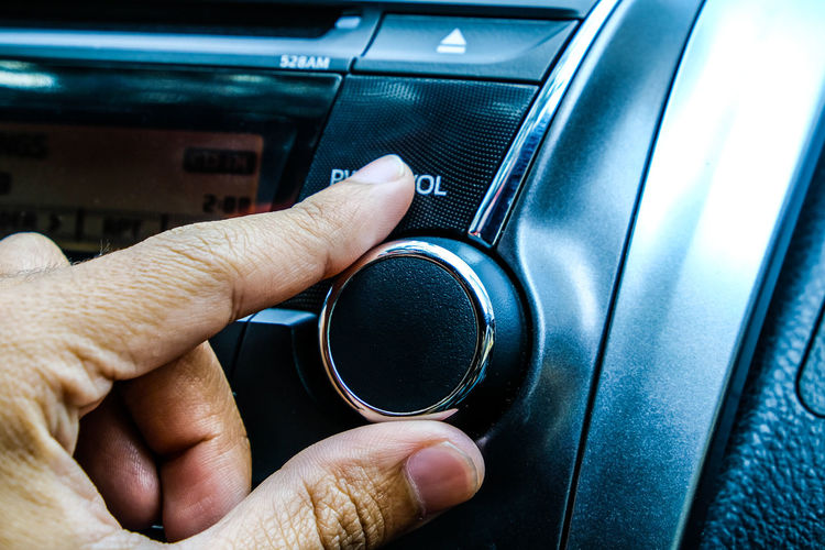 Close-Up Of Hand Adjusting Knob In Car