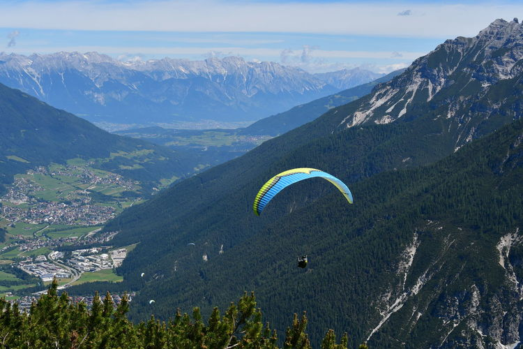 Scenic view of mountains against sky with hang glider at stubay valley