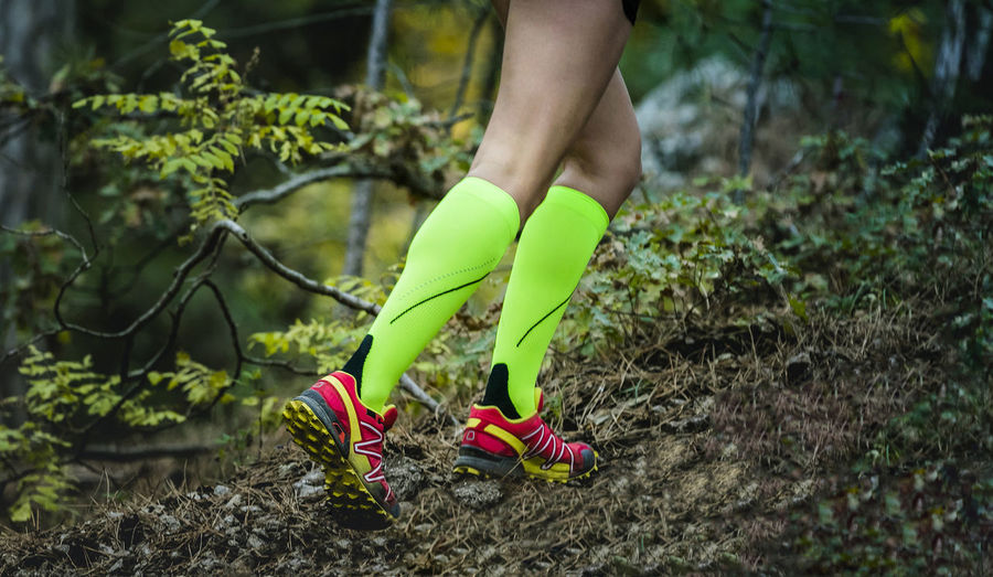 Legs female runner in bright green compression socks run uphill in forest