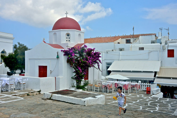 white church with red dome near a restaurant with white table outdoor and a child walking Architecture Building Exterior Built Structure Religion Sky Belief Building Place Of Worship Nature Spirituality Real People Day Dome Cloud - Sky People Outdoors City Child Church Greek Church Flowers Running Restaurant Furnitures Street View Street Photography Bouganville Flower Greek Architecture Mykonos,Greece Tourism Cityscape Street Lifestyles