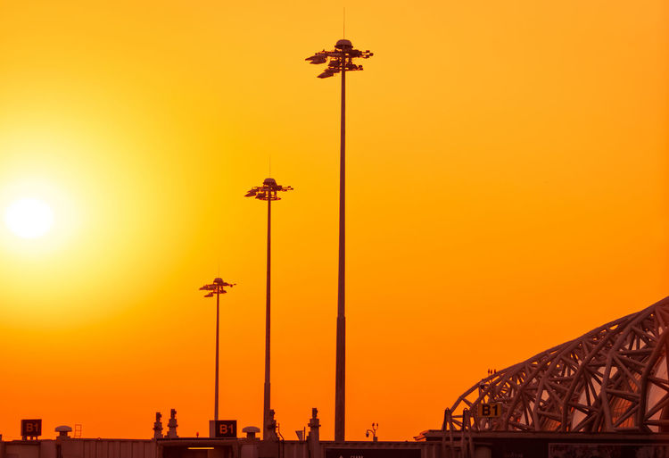 Tall electric pylon in the airport at sunset with an orange sky. spotlights pole at the airfield.