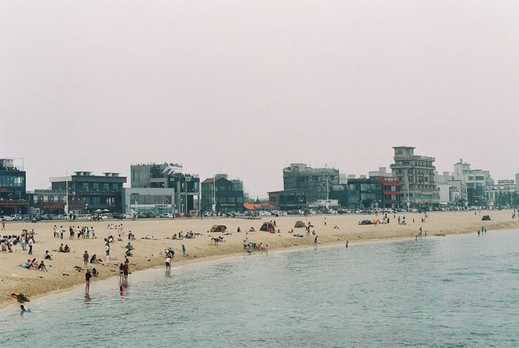 Architecture Beach Beauty In Nature Building Exterior Built Structure City Cityscape Clear Sky Day Film Film Photography Filmcamera Fm2 Korea Large Group Of People Men Nature Nikon Outdoors Real People Sand Sea Sky Vacations Water Sommergefühle