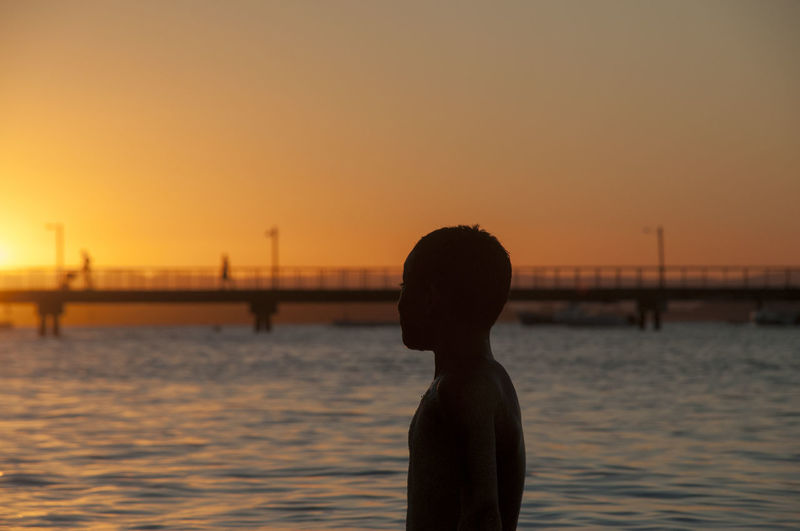 Side view of silhouette boy standing by sea against sky during sunset
