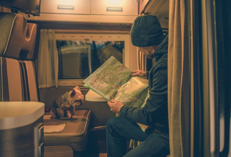 Men and His Dog Friend in the Motorhome. Animal Themes Book Camper Camper Van Day Dog Domestic Animals Indoors  Journey Mammal Mode Of Transport Motorhome People Pets Public Transportation Real People Seat Sitting Togetherness Train - Vehicle Transportation Travel Two People Vehicle Seat