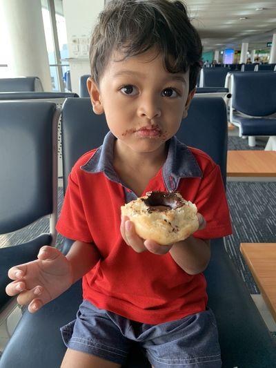 Cute boy eating food at airport terminal