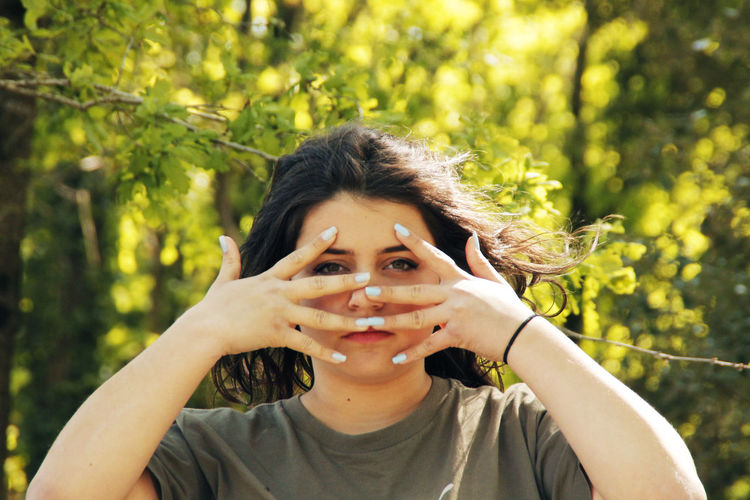 Portrait of young woman peeking through fingers against trees