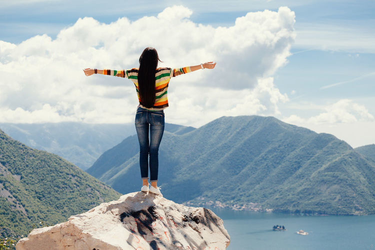 Rear view of woman with arms outstretched standing on cliff by sea