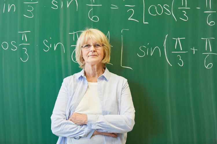 Portrait of teacher standing against blackboard in classroom