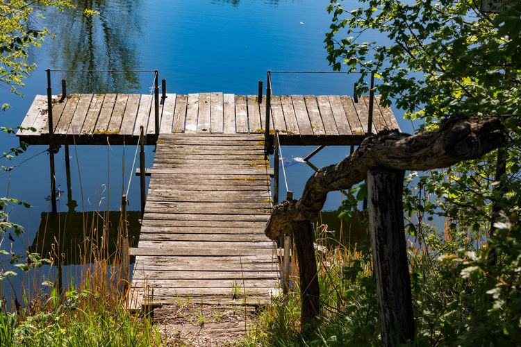 Wooden post by lake against blue sky