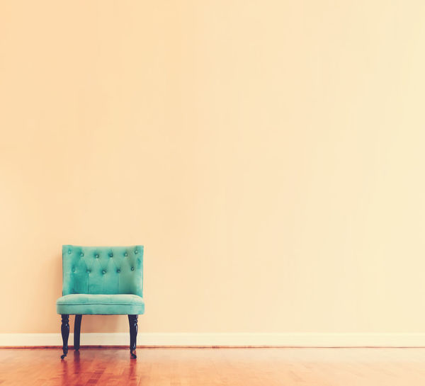 Empty chair on table against wall at home