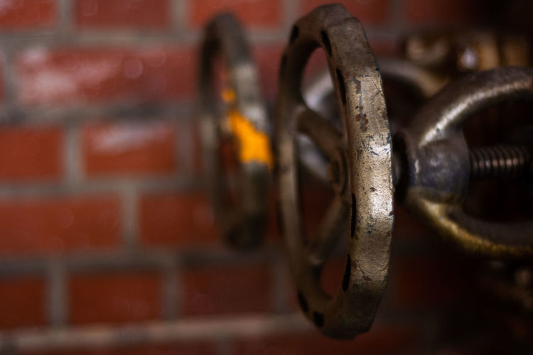 Close-up of valves against brick wall