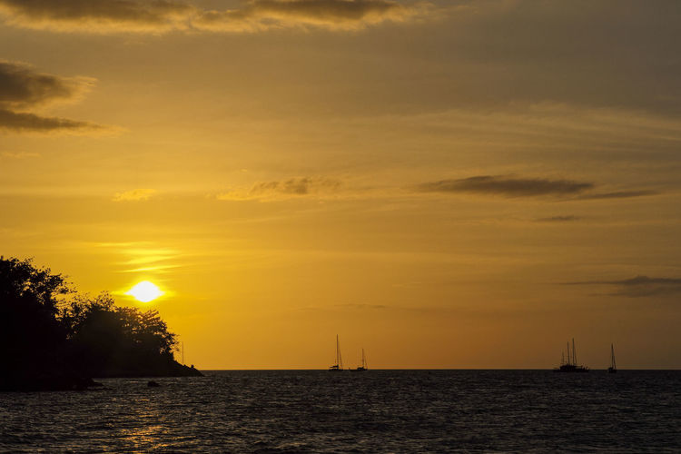 Silhouette of island and yacht boats on the horizontal line with light of sunset background