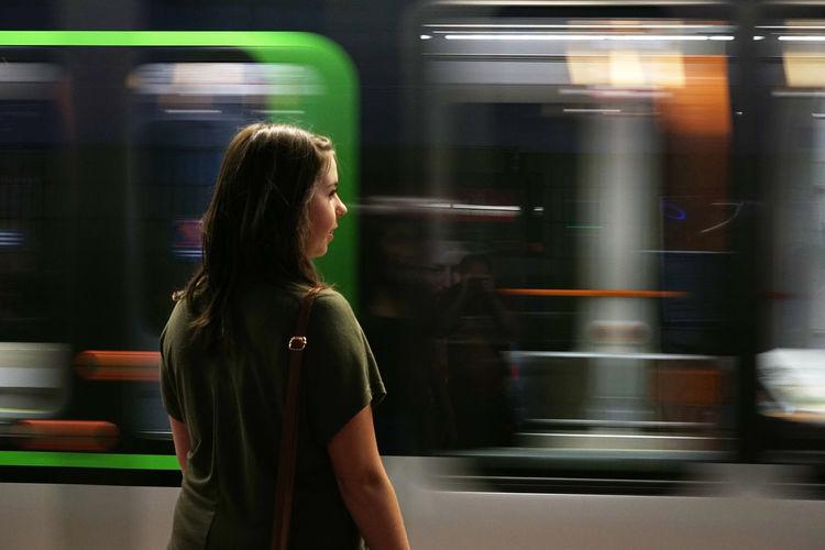 Woman looking at blur train at subway station
