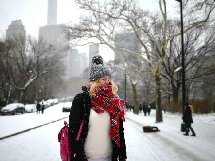 Woman wearing warm clothing while standing on snow covered footpath in city