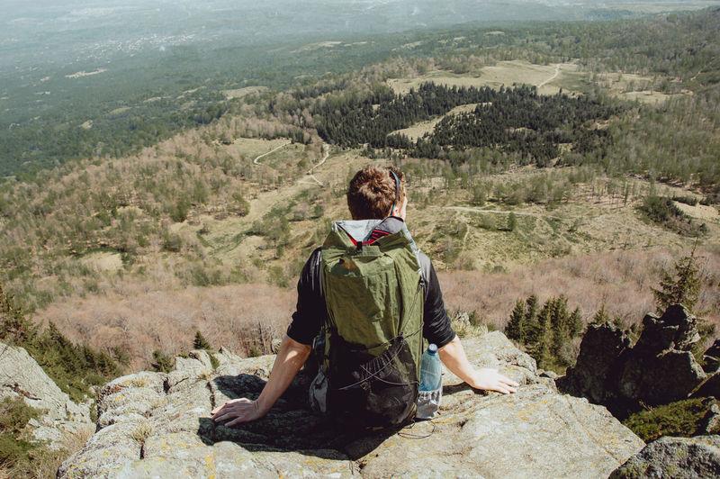 Man sitting on landscape against mountain