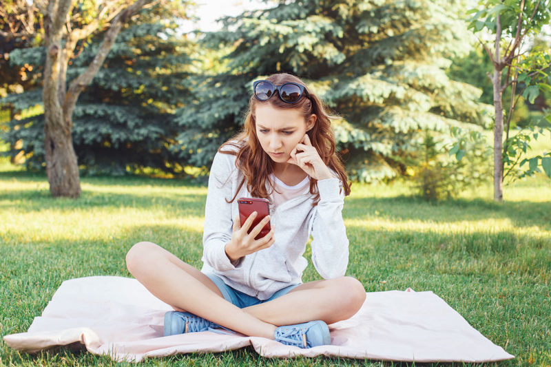 Beautiful young woman using phone while sitting on field