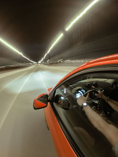 Cars moving on road in illuminated tunnel