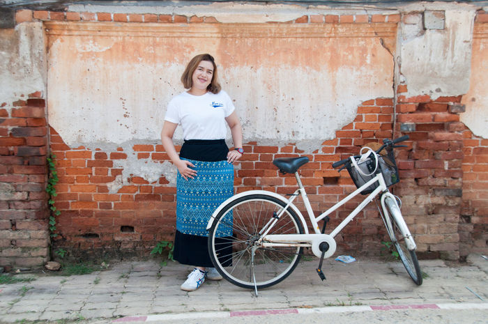 Adult Bicycle Brick Wall City Day Horizontal Leaning Lifestyles One Person One Woman Only Outdoors Pedal People Person Real People Standing Transportation Young Adult