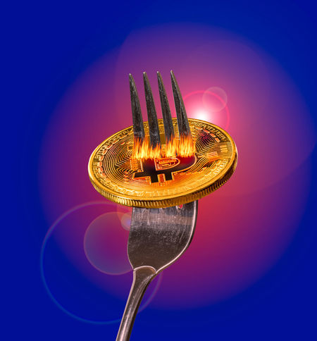 Bitcoin coin on a fork to illustrate a break or new copy of a blockchain underpinning the cyber currency Fork Growth Split Bitcoin Bitcoin Mining Bitcoins Blockchain Blockchain Concept Blockchain Technology Blue Blue Background Colored Background Conceptual Copied Cyber Currency Fork Glowing Illustration Kitchen Utensil Studio Shot