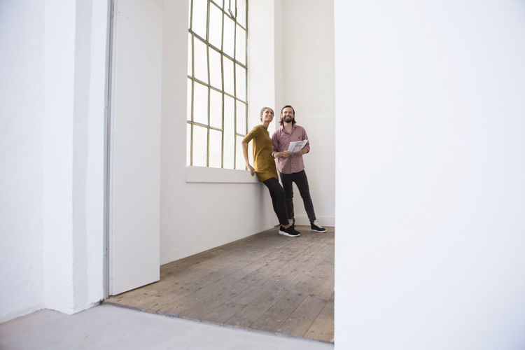 Young couple standing against wall