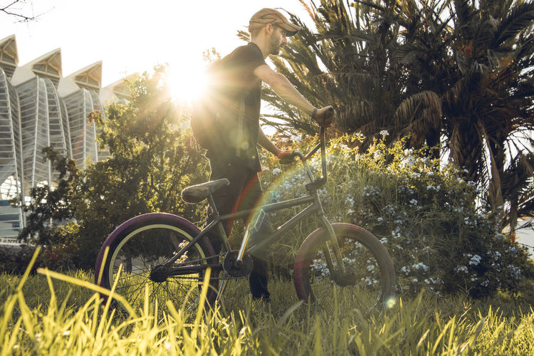 Man riding bicycle by plants against sky