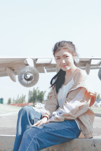 Portrait of smiling young woman sitting against clear sky
