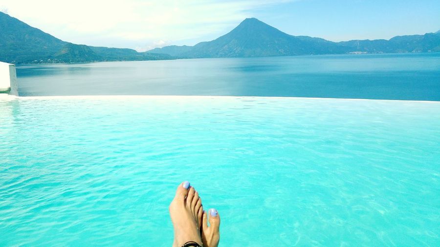 Low section of woman relaxing on infinity pool against mountain