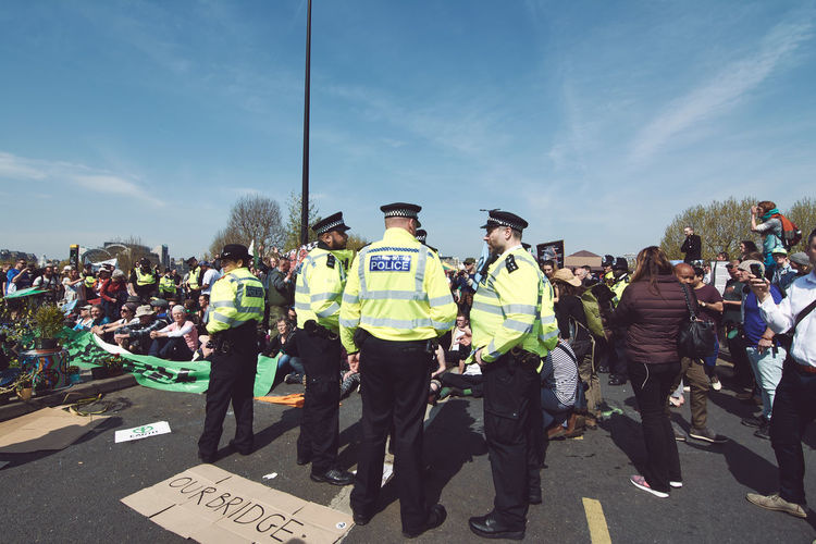 Extinction Rebellion - London 2019 Extinction Rebellion Protest Protesters London Group Of People Safety Text Day Real People Crowd Men Occupation Clothing Large Group Of People Uniform Sky Reflective Clothing Nature Responsibility Road Protection Helmet Police Force Outdoors Government