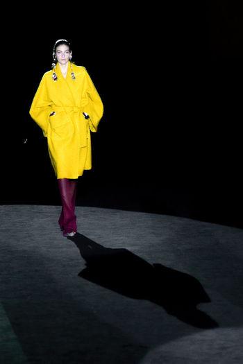 Portrait of person standing on yellow umbrella