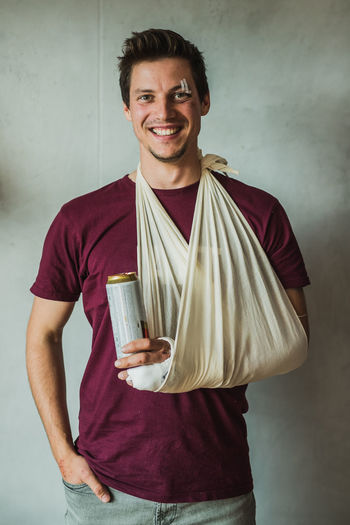 Portrait of smiling young man with fracture hand holding alcohol can while standing against wall