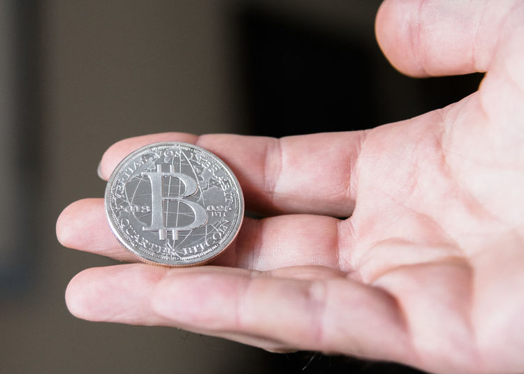 A minted Bitcoin in silver close up in hand color. Banking Bitcoin Close-up Coin Color Cryptocurrency Day Digital Digital Currency Fingers Future Holding Human Body Part Human Hand Indoors  Investing Management Minted One Person People Quarter  Real People Silver  Technology Wealth