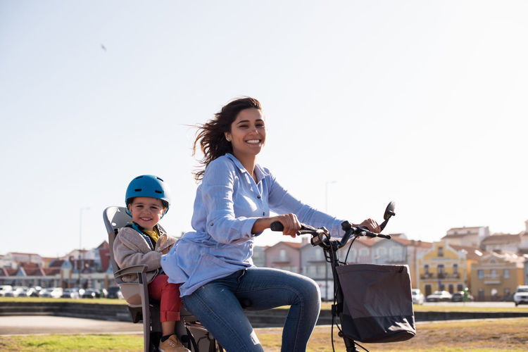 Portrait of smiling woman riding bicycle against clear sky