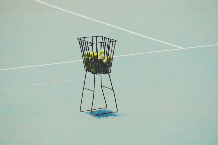 Tennis balls in basket on court during sunny day