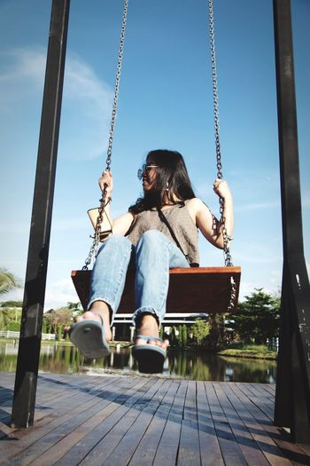 Rear view of woman sitting on swing at playground
