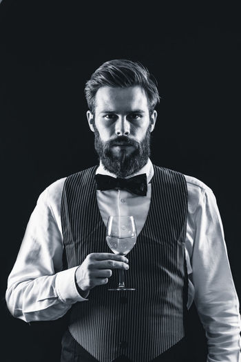 Portrait of bartendar holding wineglass in bar