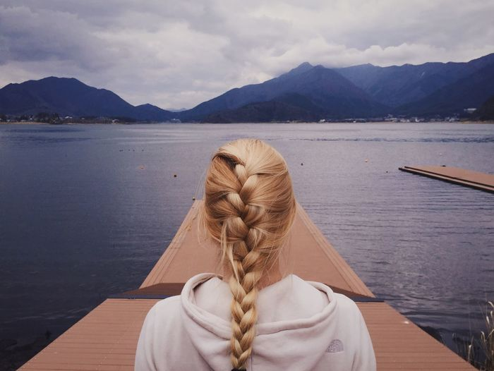 Rear view of braided woman on pier at lake