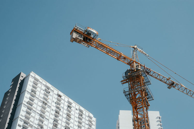 Low angle view of tower crane against blue sky