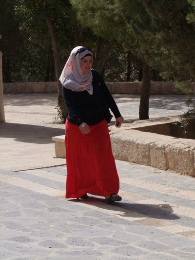 Jordanian Woman, Mount Nebo Adult Composition Front View Full Frame Full Length Jordan Jordanian Beauty Lifestyles One Person One Woman Only Outdoor Photography Real People Red And Black Colour Sunlight And Shadow Traditional Clothing Tree Walking Alone... Woman Woman Portrait